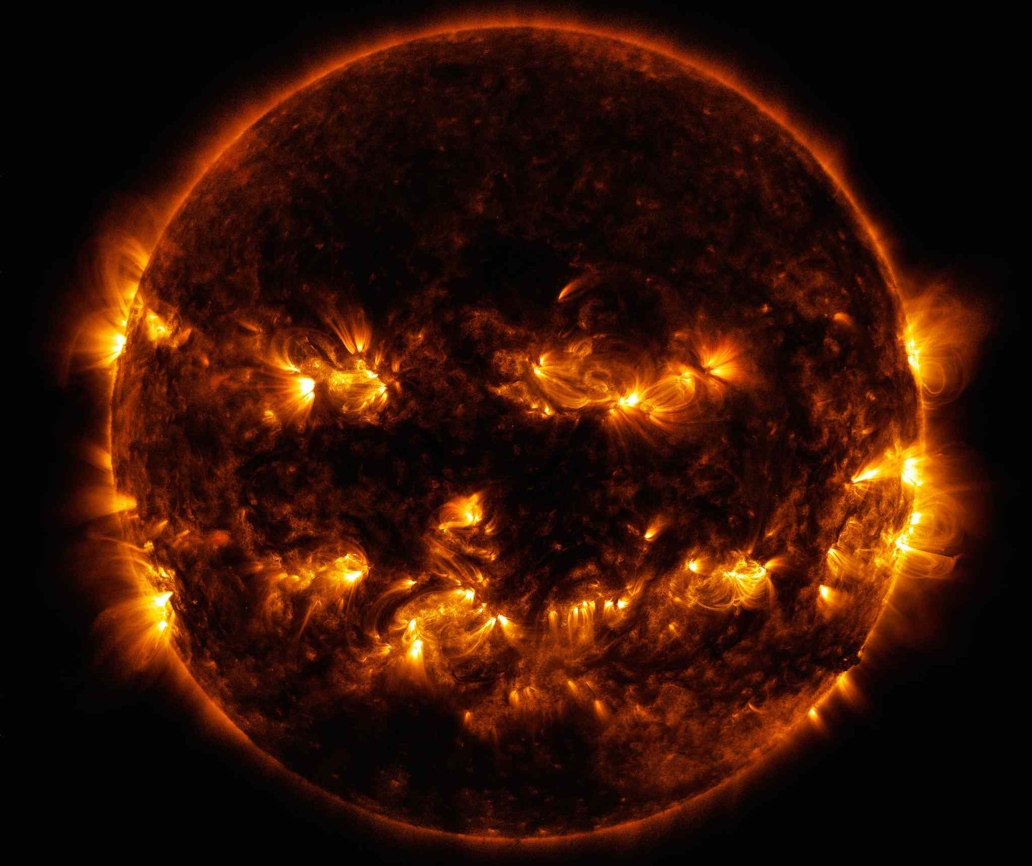 Close up photo of the sun from space with flames around the sides and center forming what resembles a smiling face