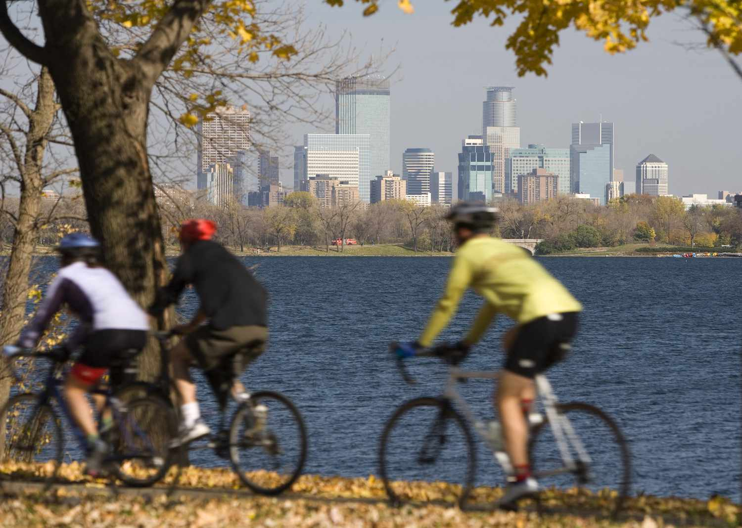 Three bicyclists ride past a waterfront in Minneapolis