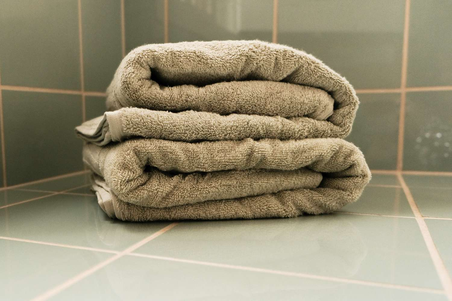 stack of green towels in tiled bathroom