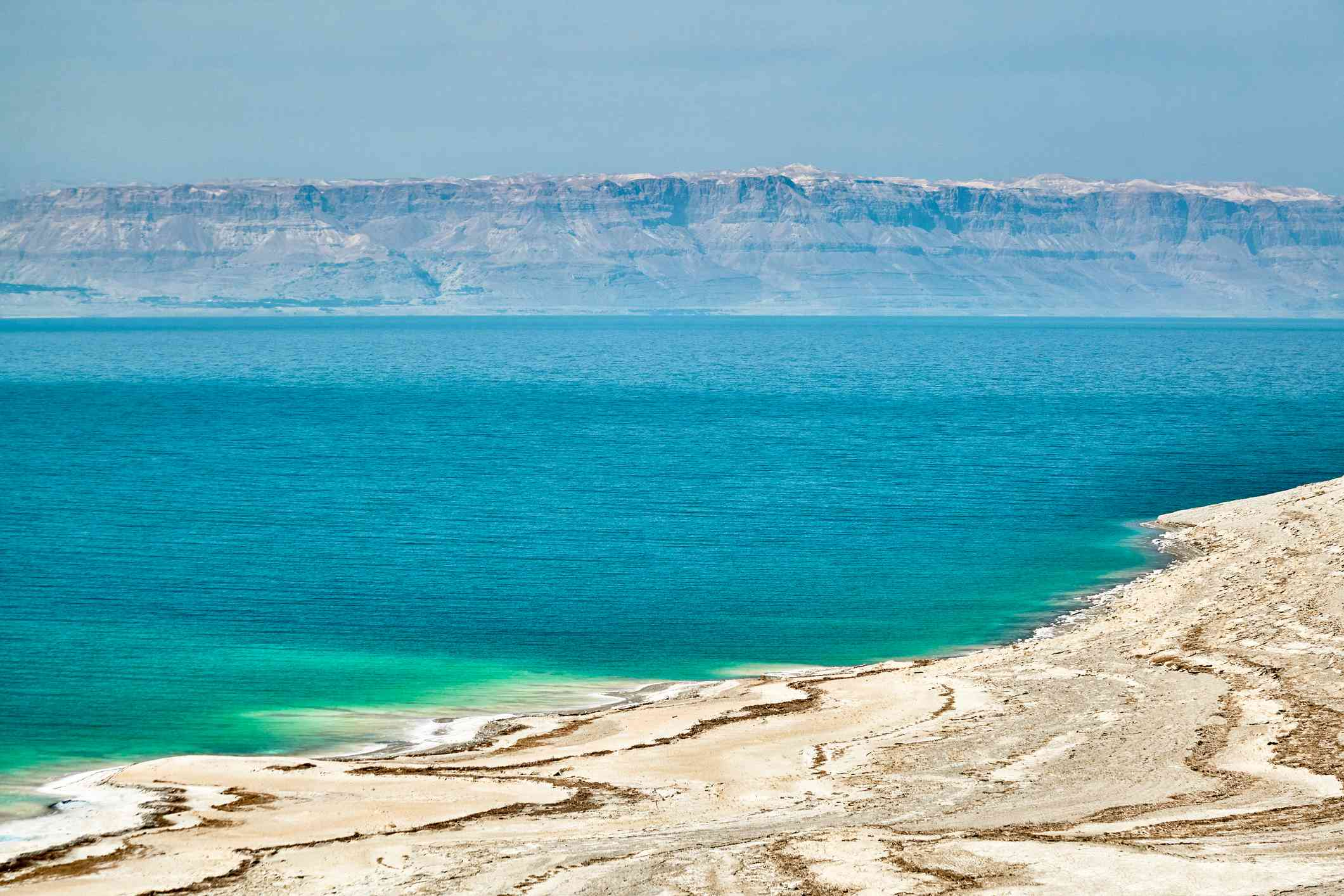 A brilliant blue lake with white salt deposits on its sandy shores