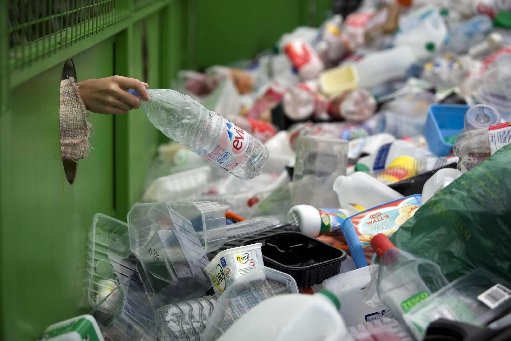 A hand puts a plastic bottle into a bin full of bottles.
