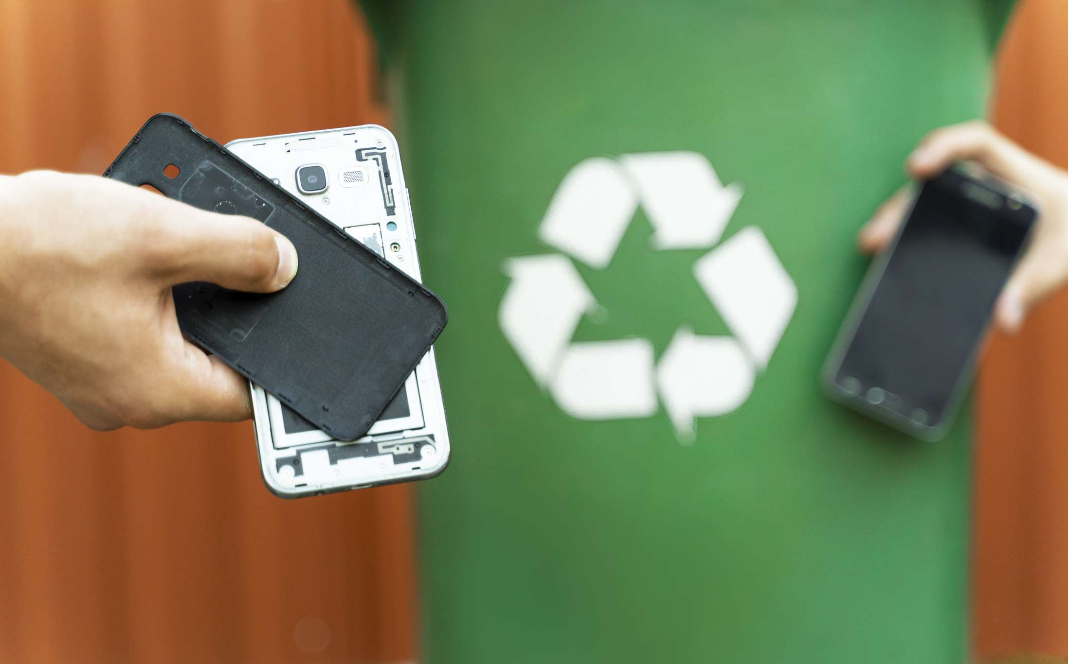 An old cell phone being brought to a green recycling bin.