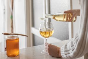 person in sweater pours honey mead into wine glass