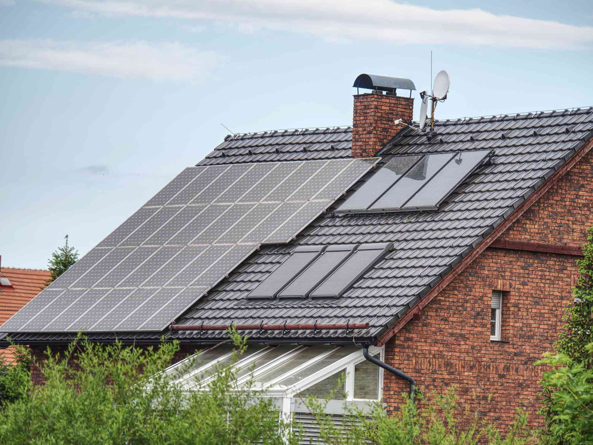 Solar panels on a roof of a brick house.