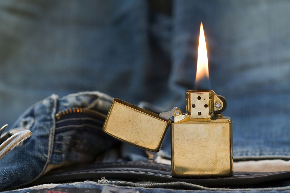 A closeup image of a Zippo lighter on some jeans.