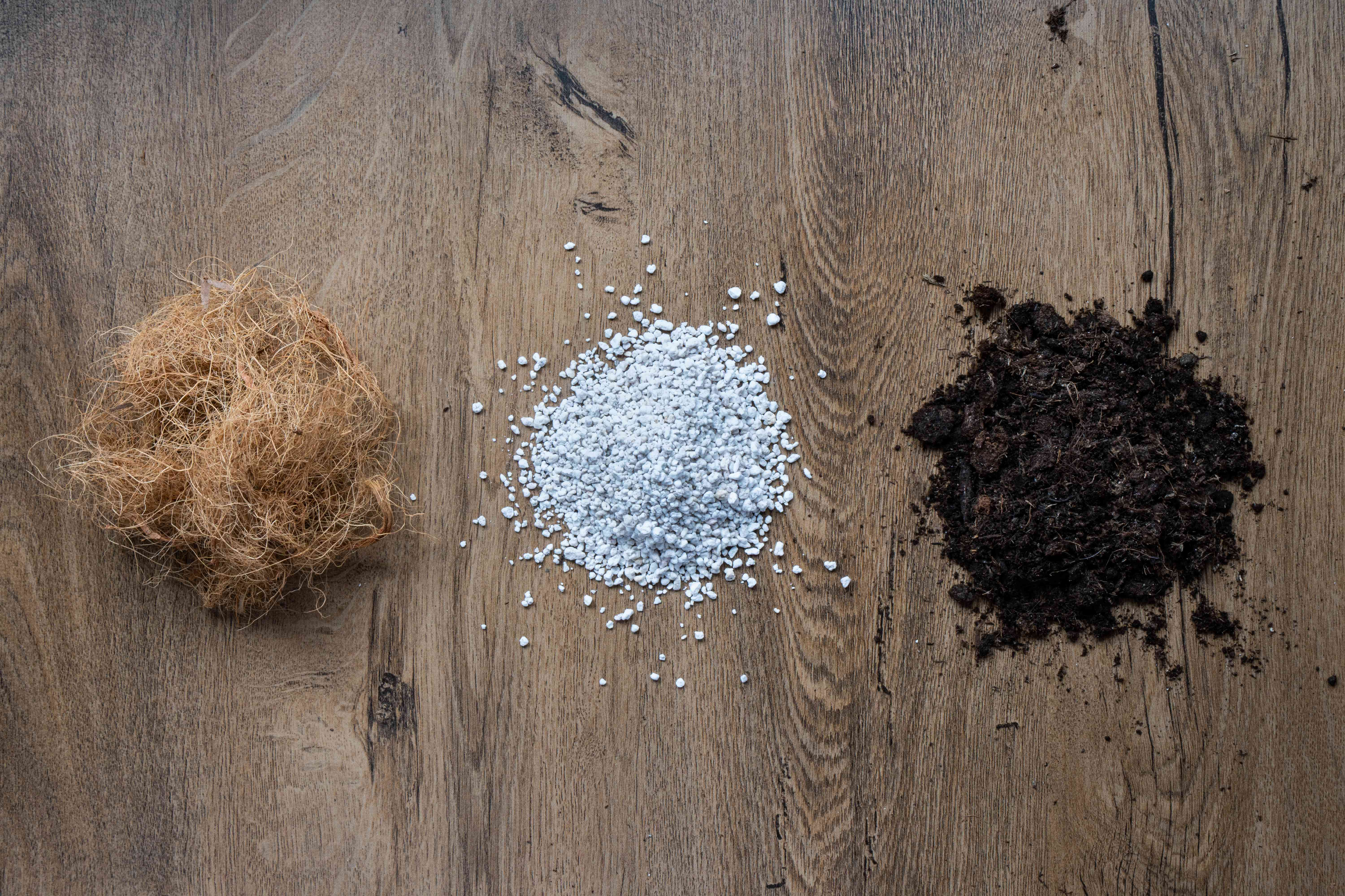 coir, vermicompost and perlite mixtures in three small piles on wood floor