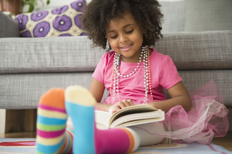 African American girl reading in living room