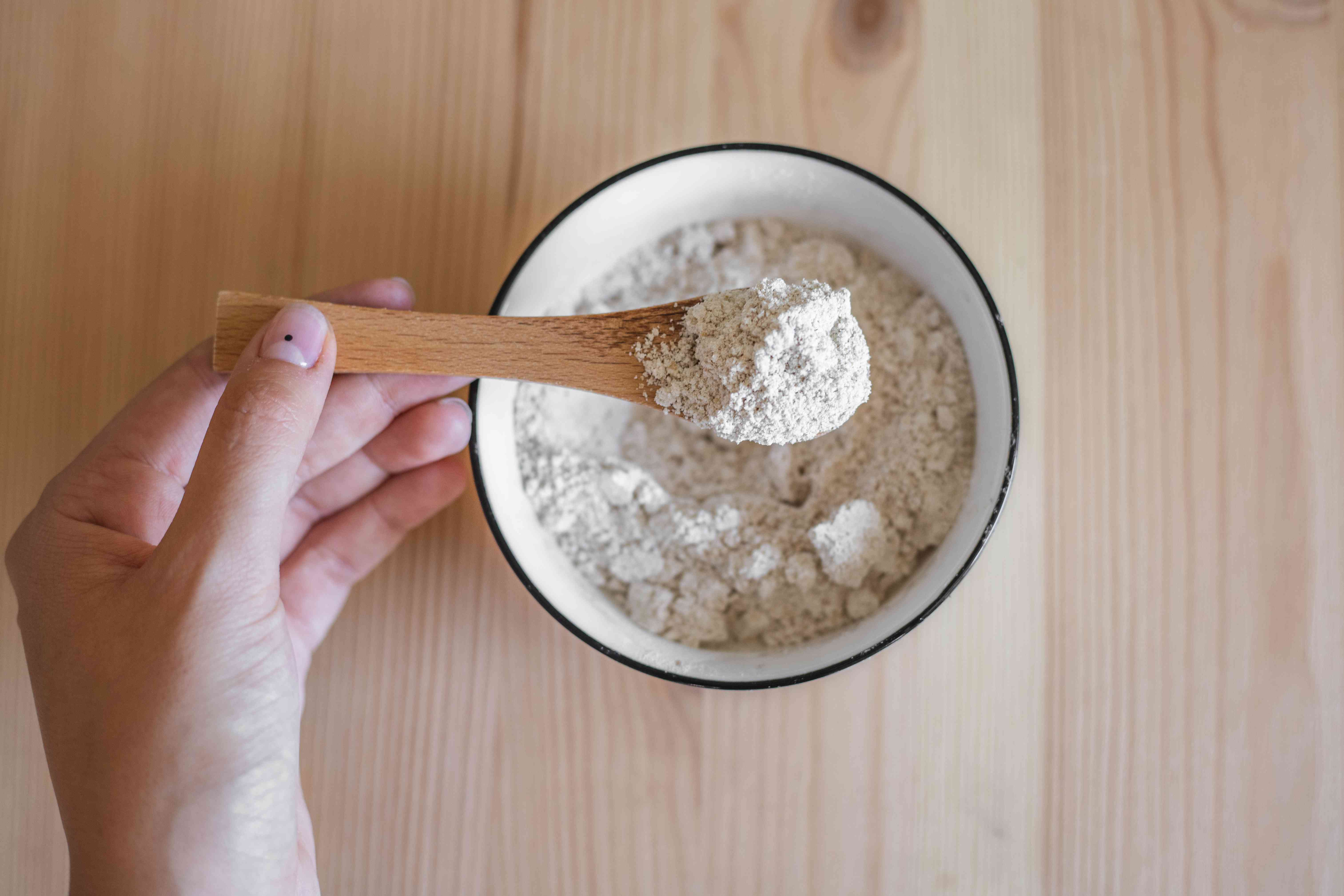 hand holds up wooden spoon filled with smoothly ground colloidal oatmeal