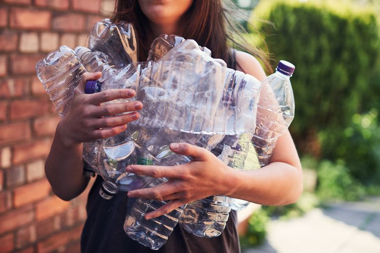 A woman holding empty plastic water bottles.