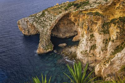 A cave entrance and natural arch along the coastline