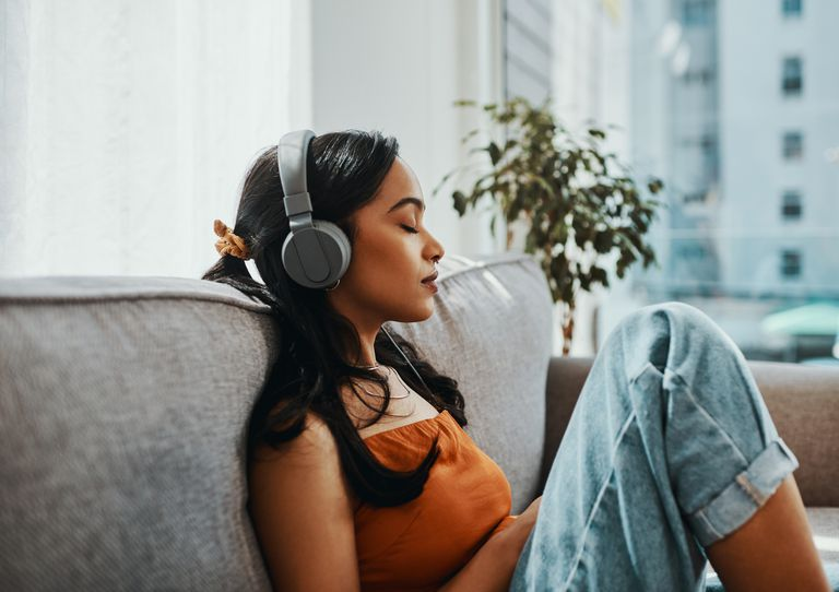 Woman sitting on a sofa with headphones on