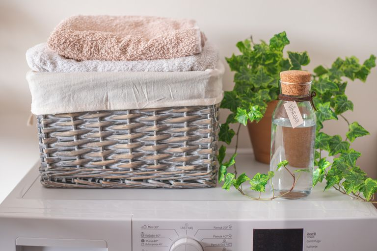 washing machine with glass bottle of vinegar, laundry basket with towels, and ivy plant