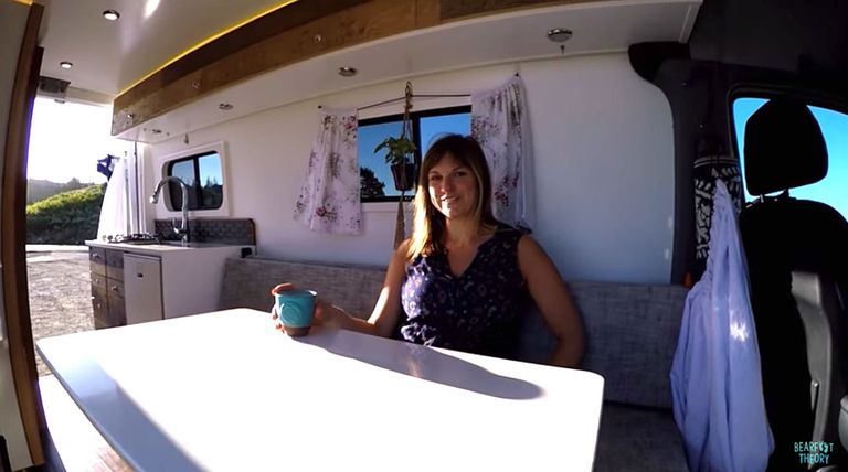 Woman sits in converted home on wheels