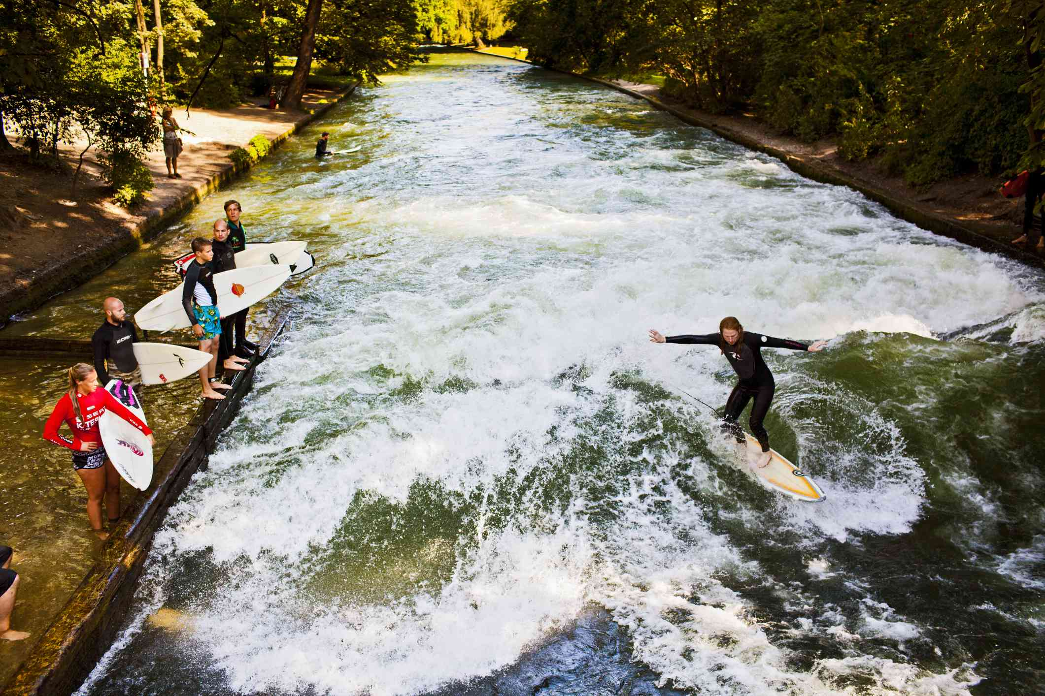 Bright green water of the Eisbach River with one surfer riding a wive while other surfers holding boards stand on a platform nearby, further down the river, the banks covered with green foliage on a sunny day