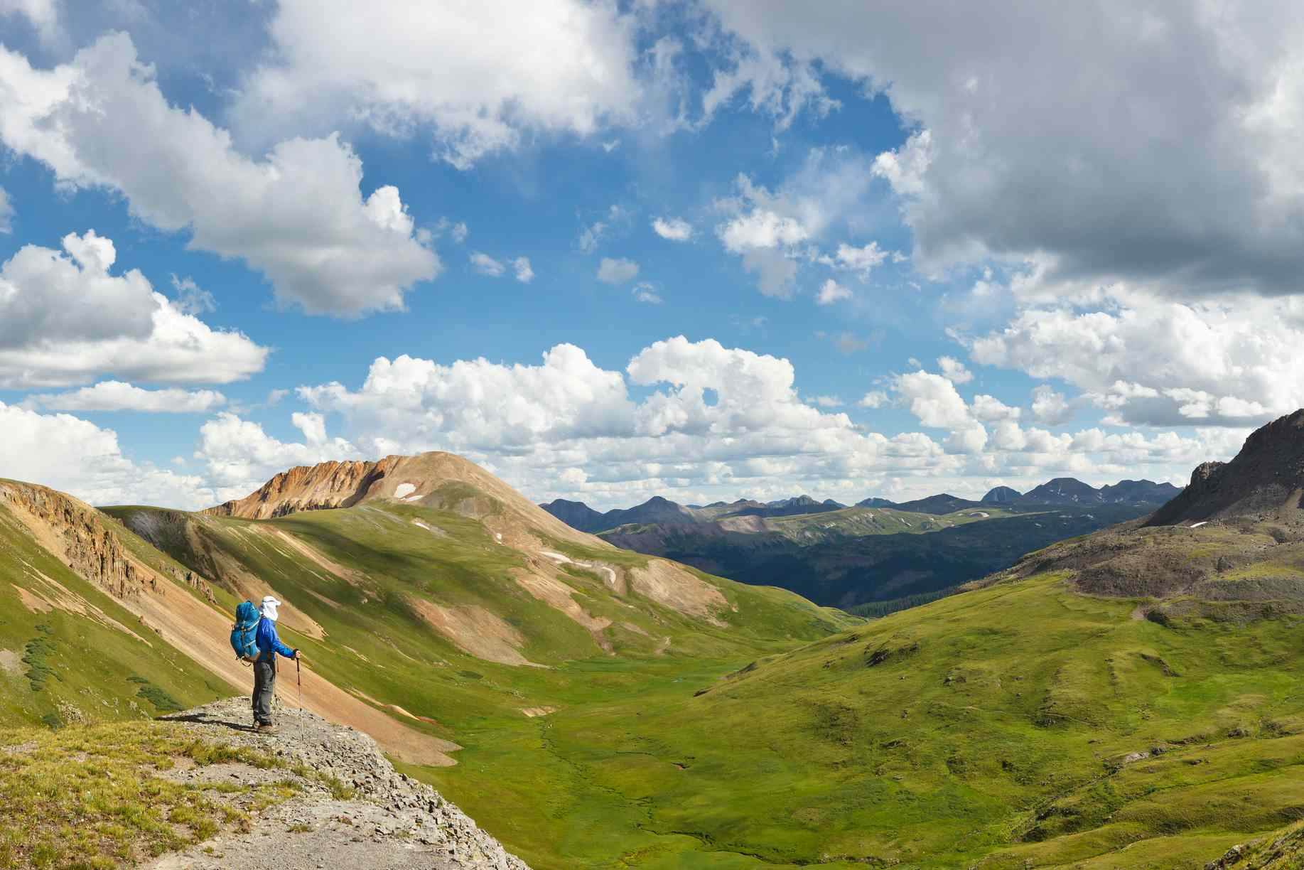 Hiker looking out over Colorado mountains from a viewpoint