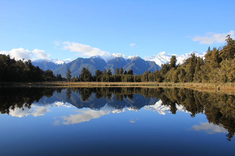 The mountains and forest of Westland Tai Poutini National Park reflected in Lake Matheson with a clear blue sky and a few low, white clouds