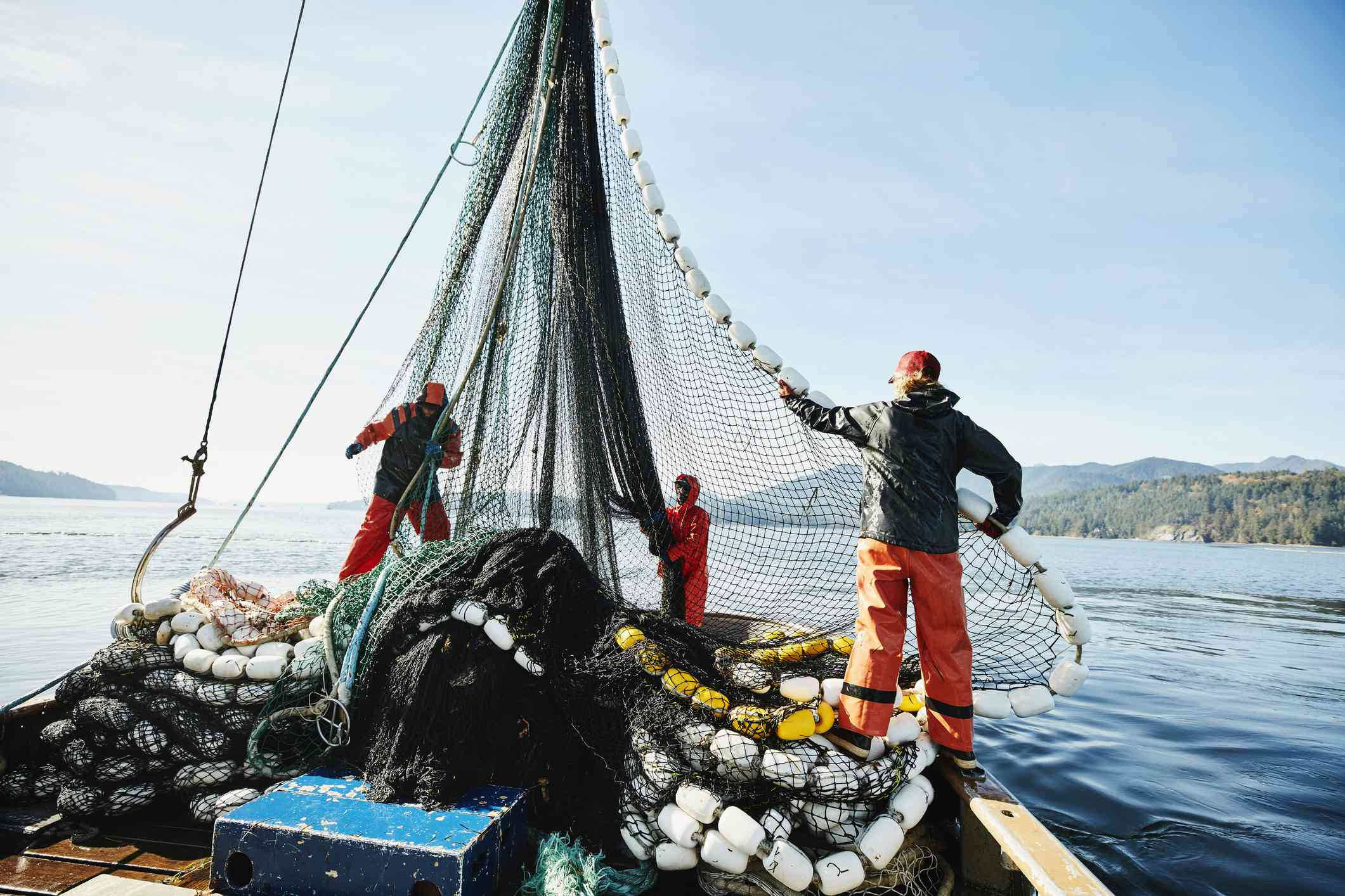 Fishers maneuvering a fishing net on a commercial fishing vessel.