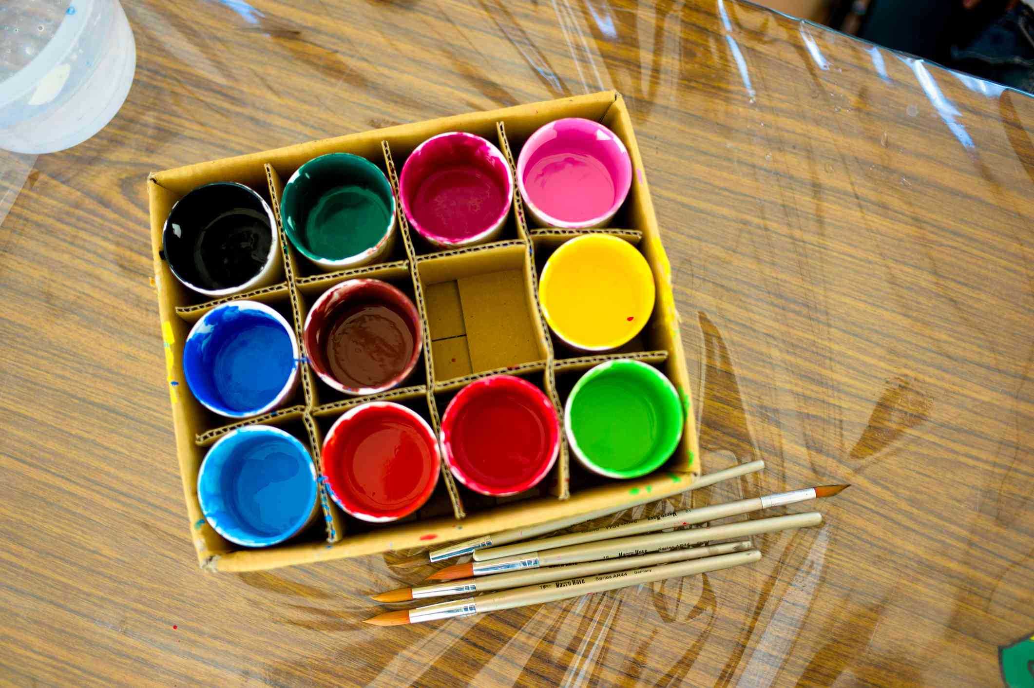 Cups of paint in a cardboard box