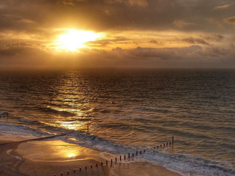 Cloudy sunrise above Southbourne Beach along southern coast of England