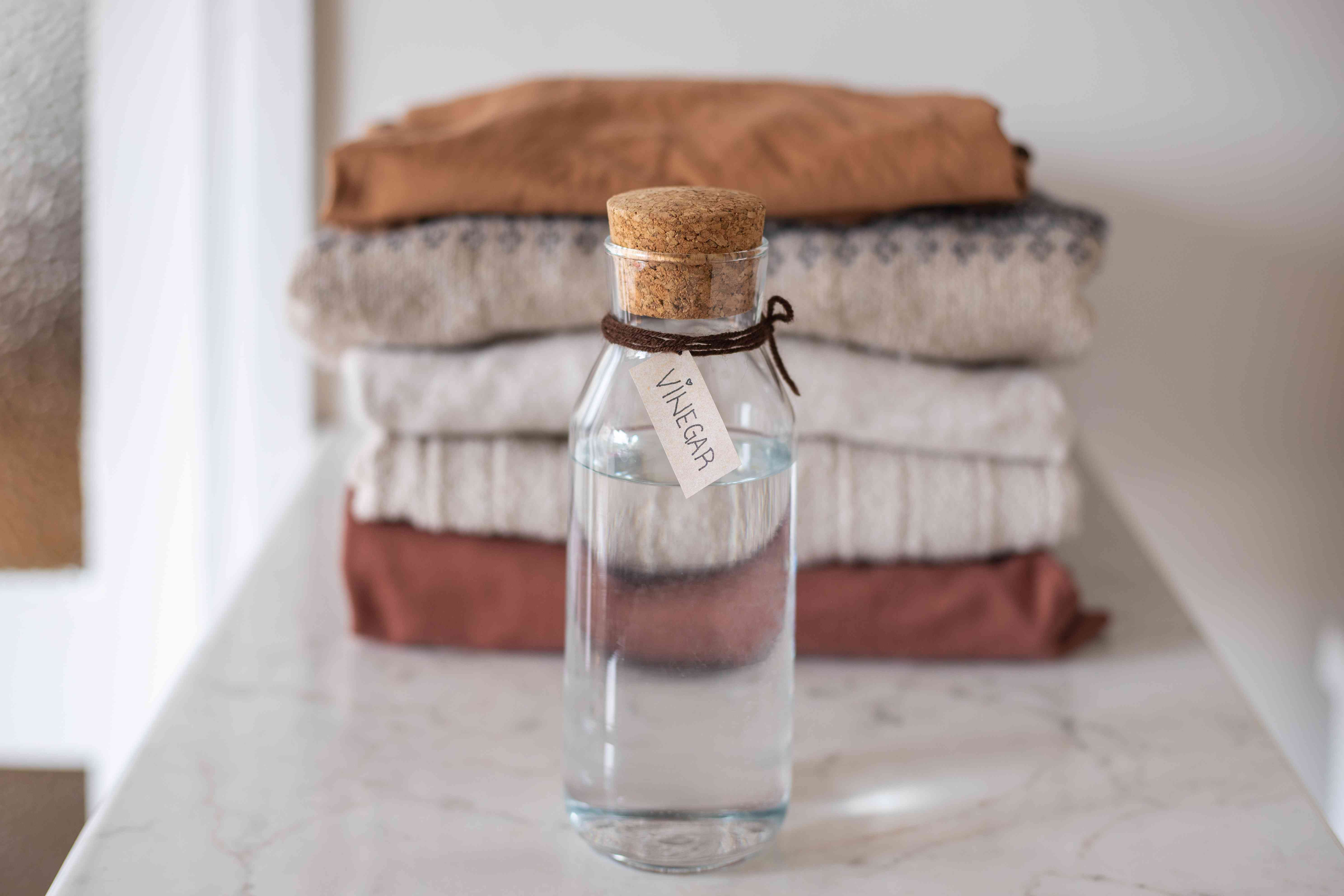 glass jar of white vinegar with stack of folded clothes behind it