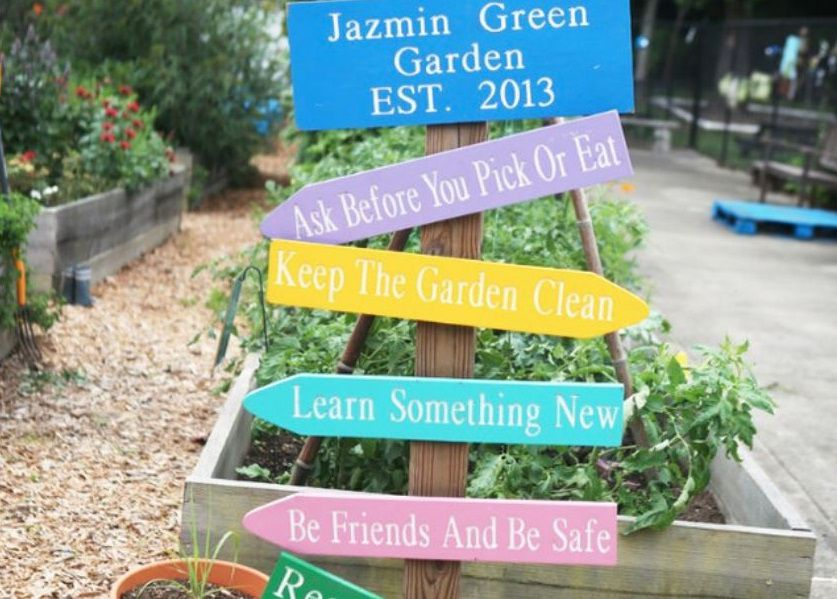 Colorful signs with thoughtful messages mark the preschool's garden.