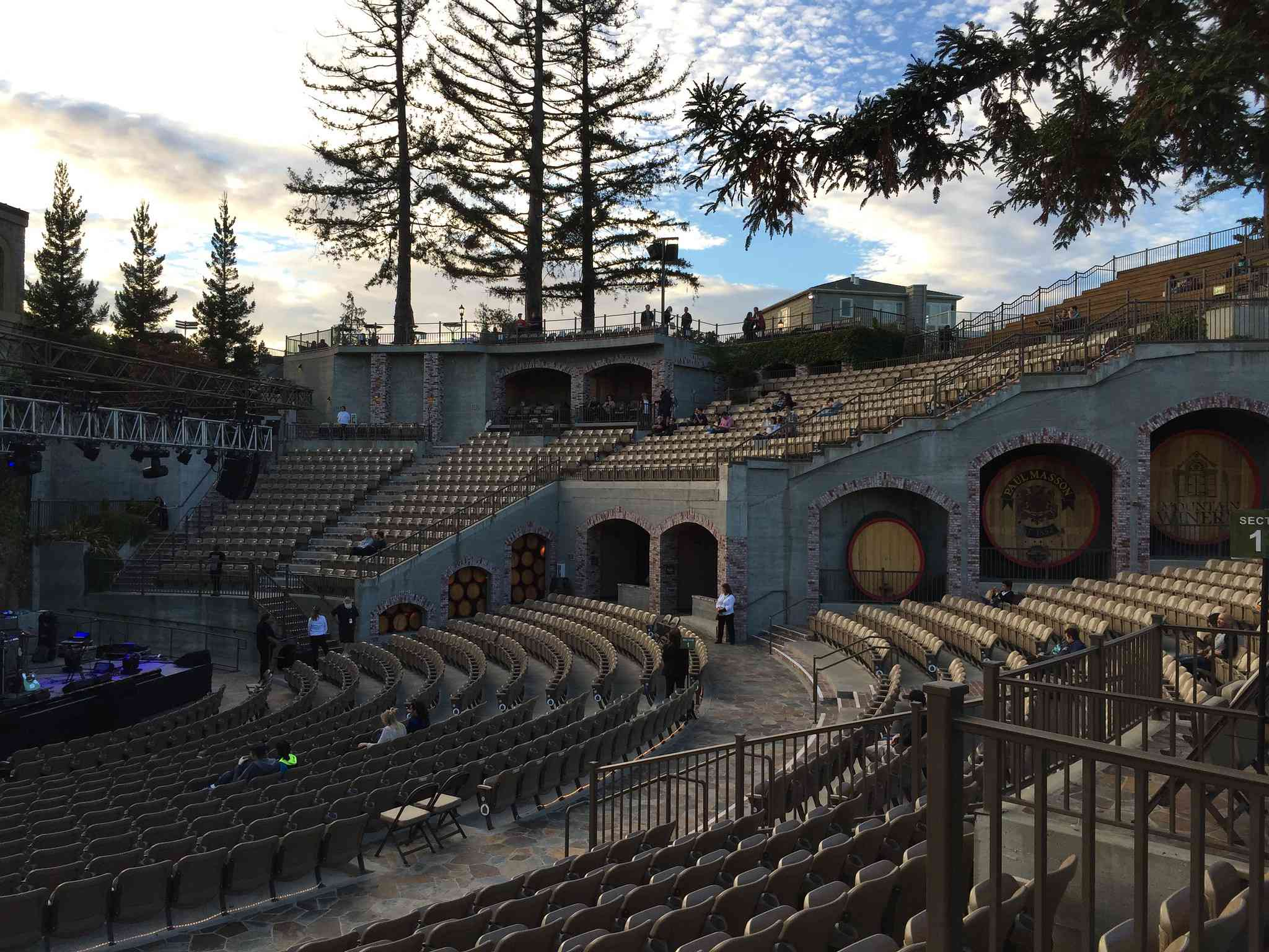 View of Mountain Winery with multi-level seating, historic buildings, and large pine trees with blue sky and white clouds above