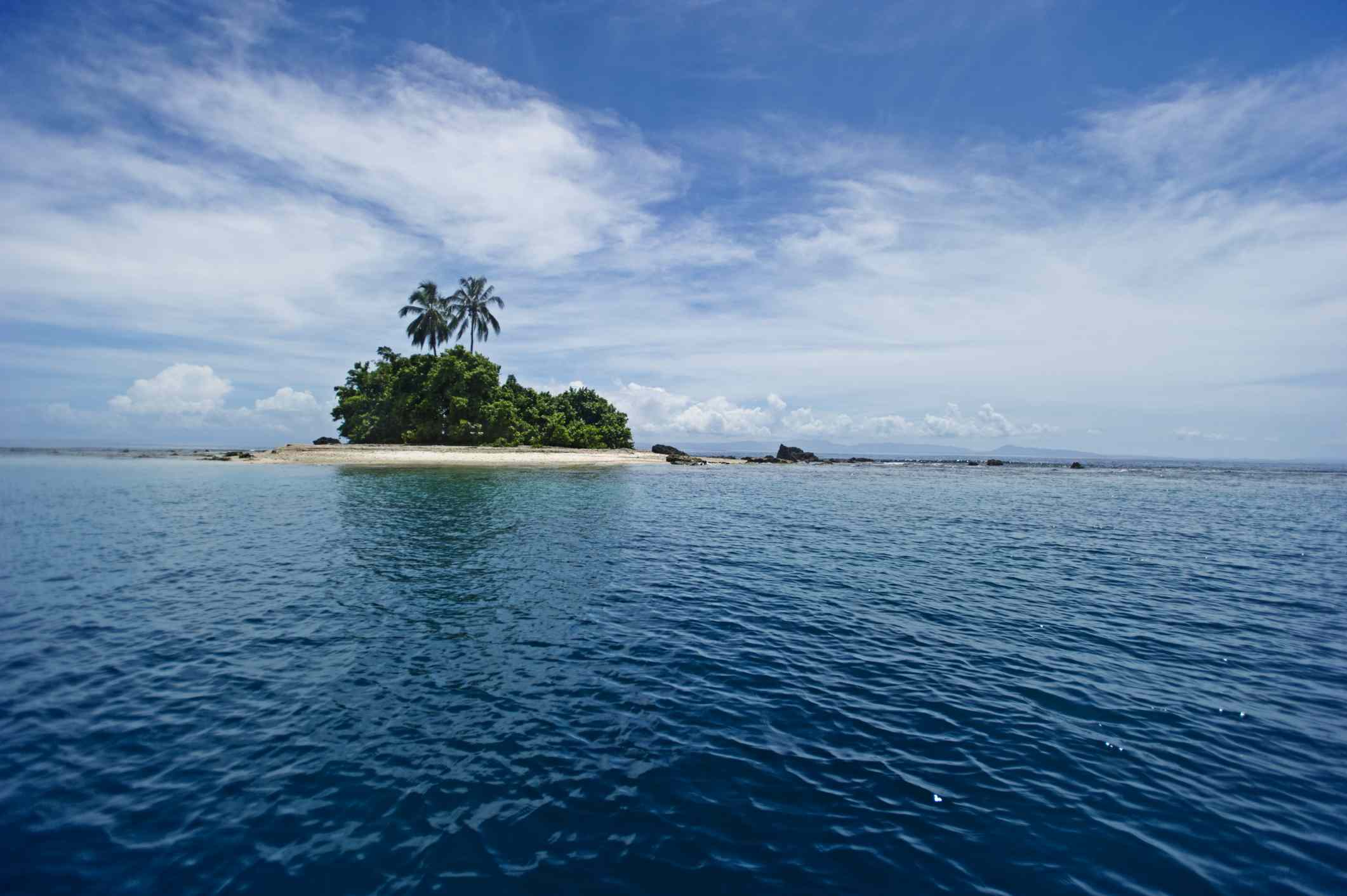 Tetepare Island with white beaches and palm trees in the distance as viewed from across the Pacific Ocean