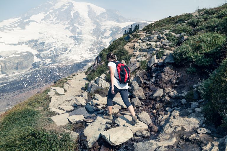 Hiker walking on rocky trail with Mount Rainier in background