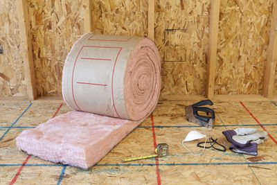 A roll of insulation being installed in a room.
