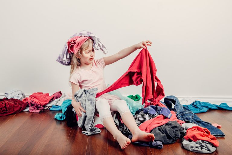 Little girl in a pile of clothes