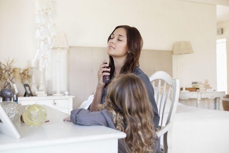 A woman spraying fragrance on her neck as her daughter watches.