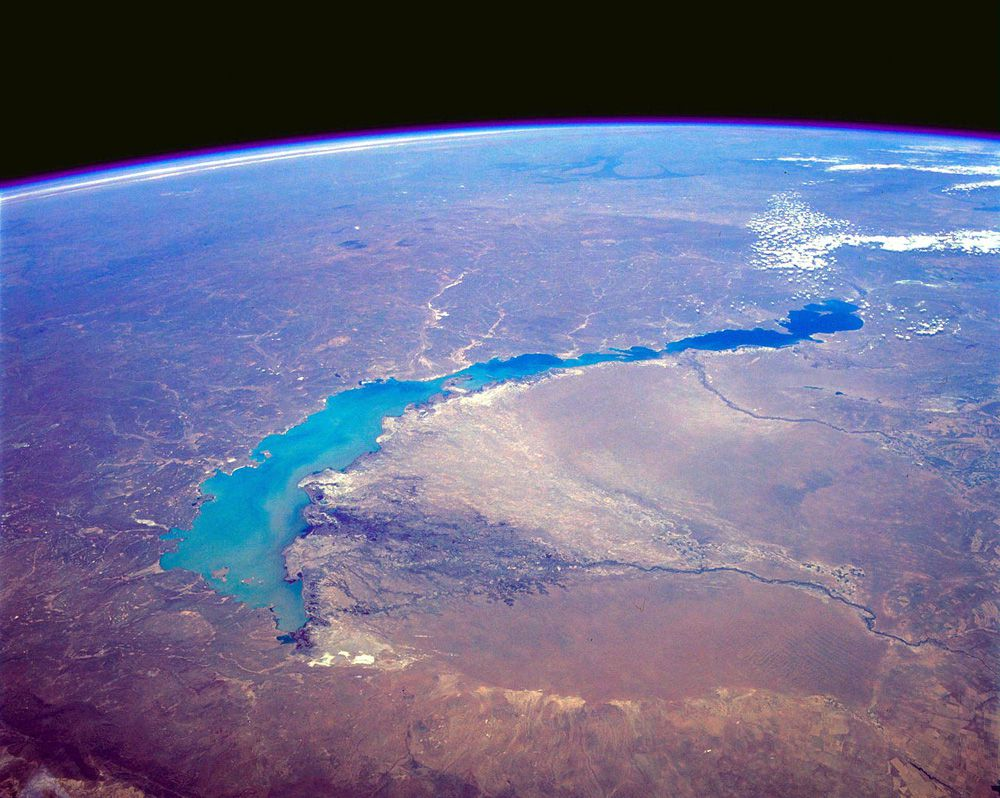 An extremely high angle view of a long, narrow lake and the curvature of the Earth