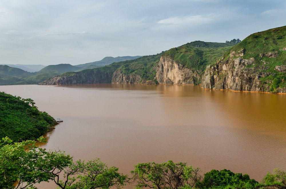 A reddish brown lake ringed by cliffs and trees