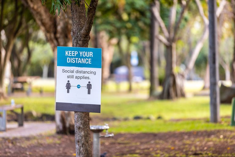 A social distancing sign attached to a tree in a park.