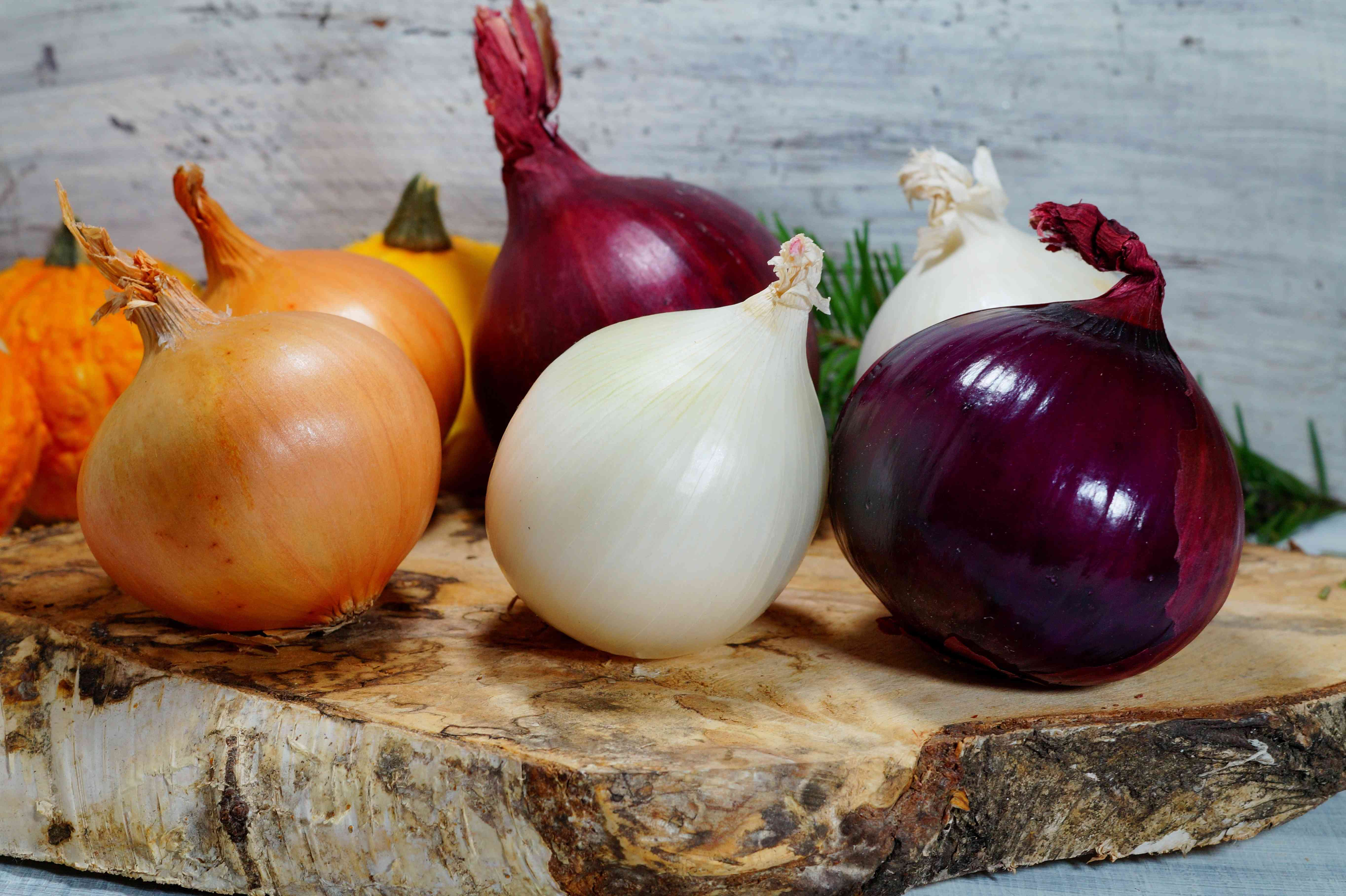 white, yellow, and red onions on a natural wood cutting board