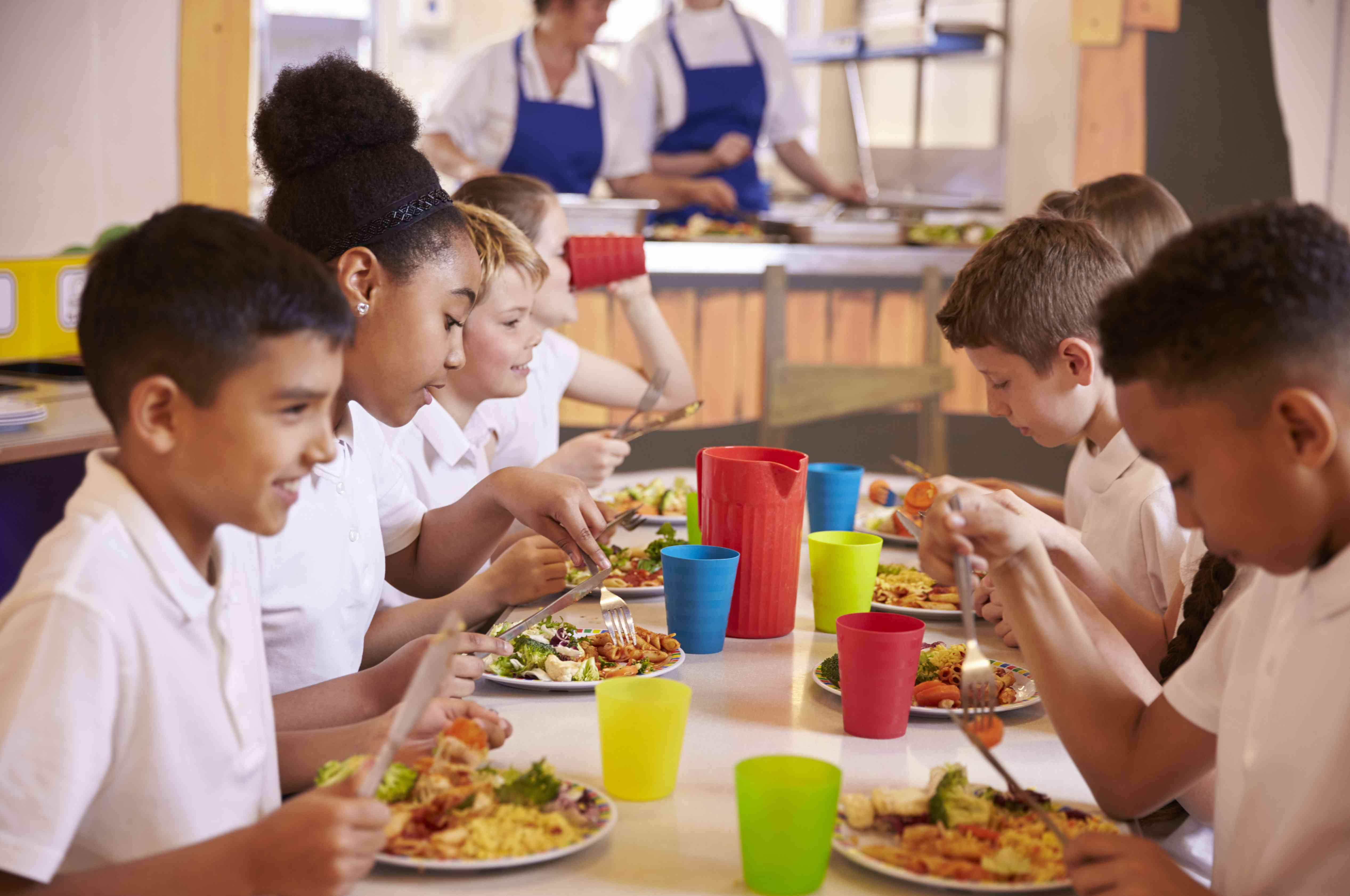 group of kids at table eat school lunch