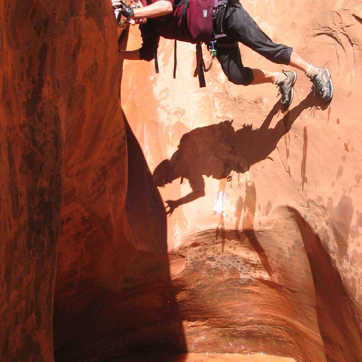A man shimmies down a canyon wall in Utah