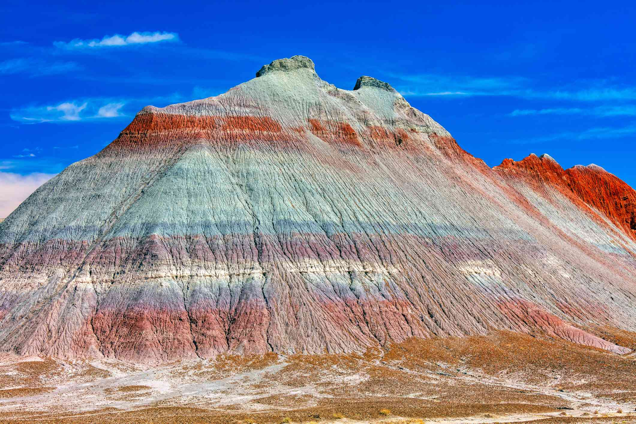 A mountain in the desert with layers of red, gray, blue, and purple stone