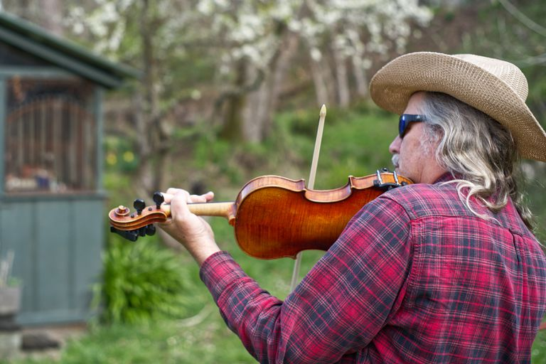 back shot of older man with long grey hair and cowboy hat playing the fiddle outside