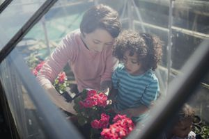 Mother planting flowers in a greenhouse with two children