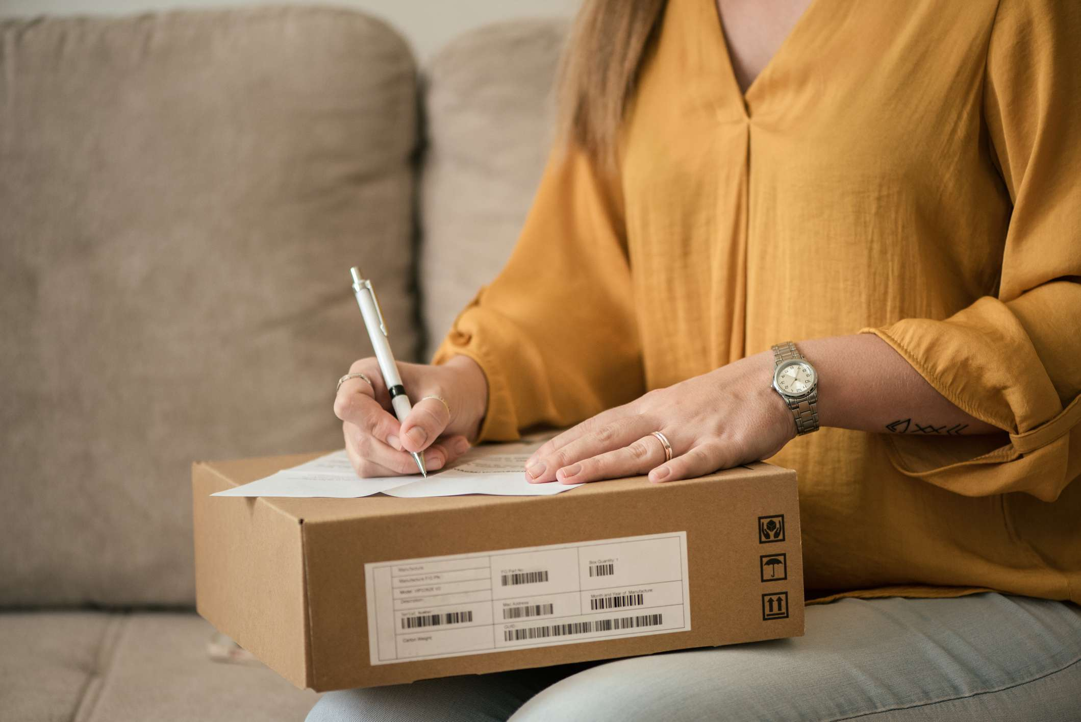A woman writing a return for a package.