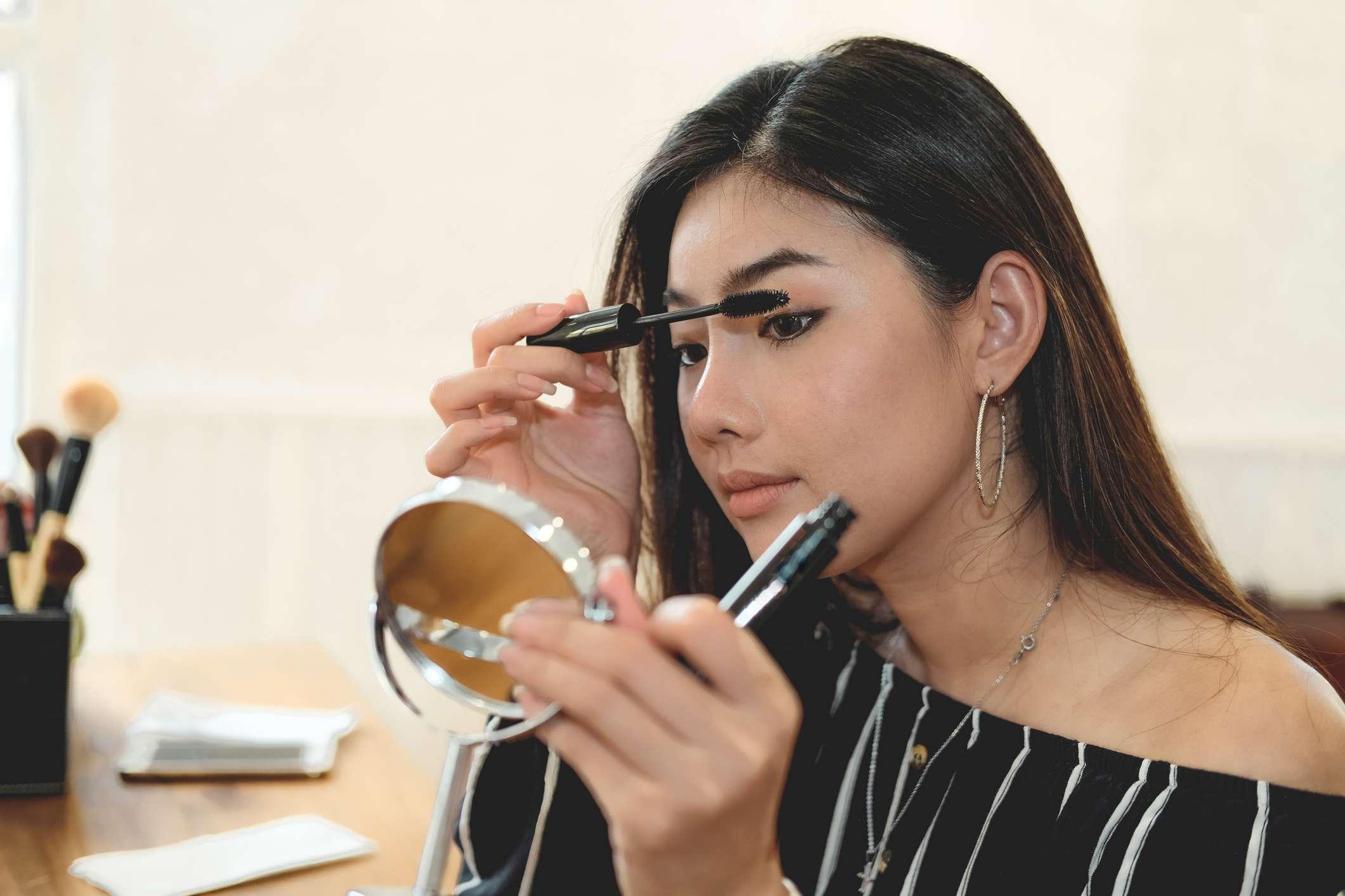 A young Asian woman applies mascara in a mirror.