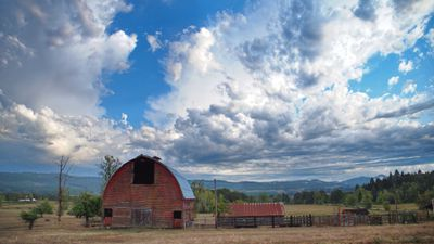 small homestead with classic red barn and brilliant blue sky with clouds