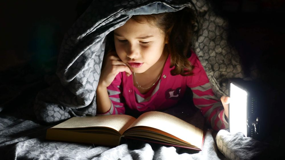 child reading with flashlight under the covers