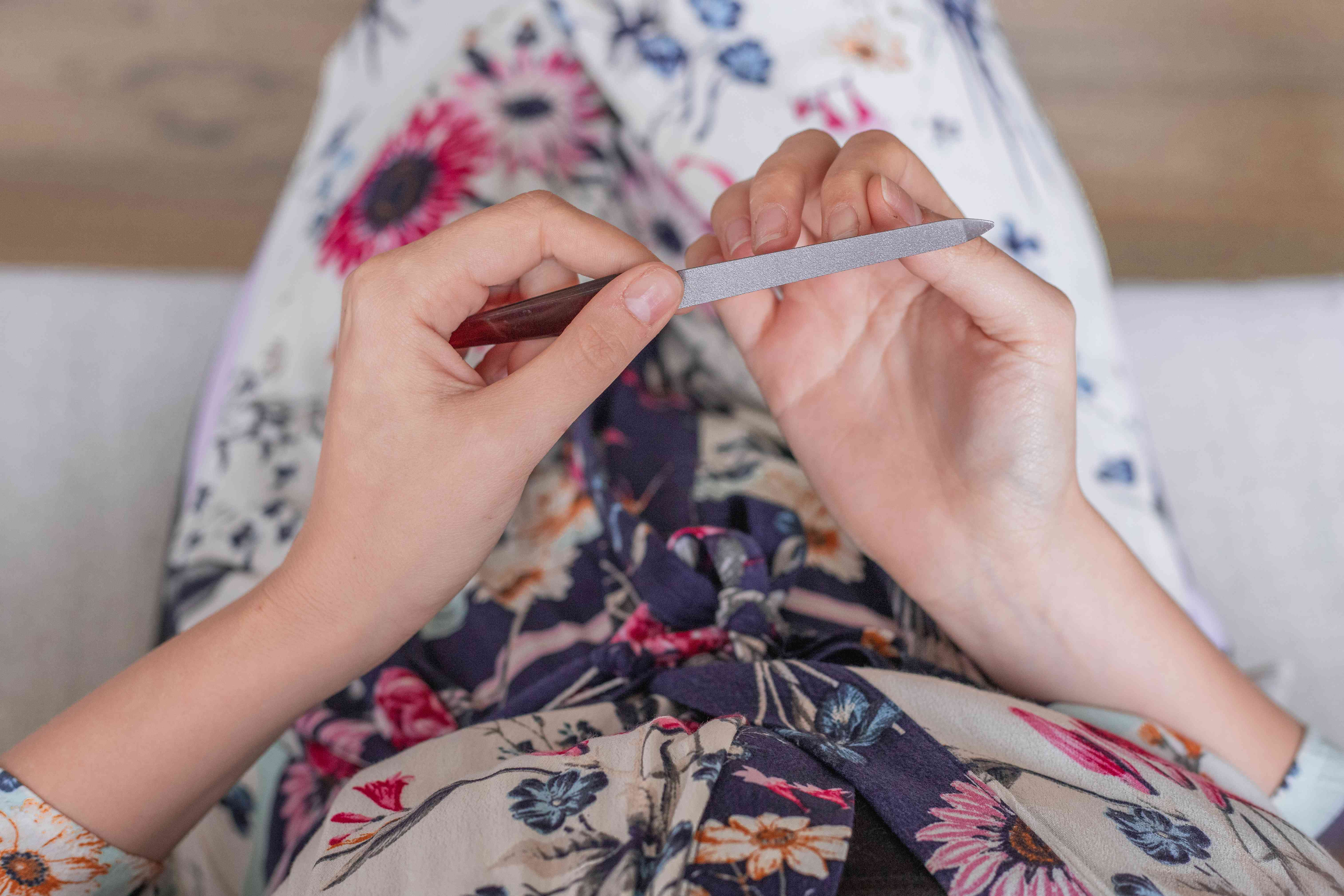over shoulder shot of person in floral dress filing nails with metal file