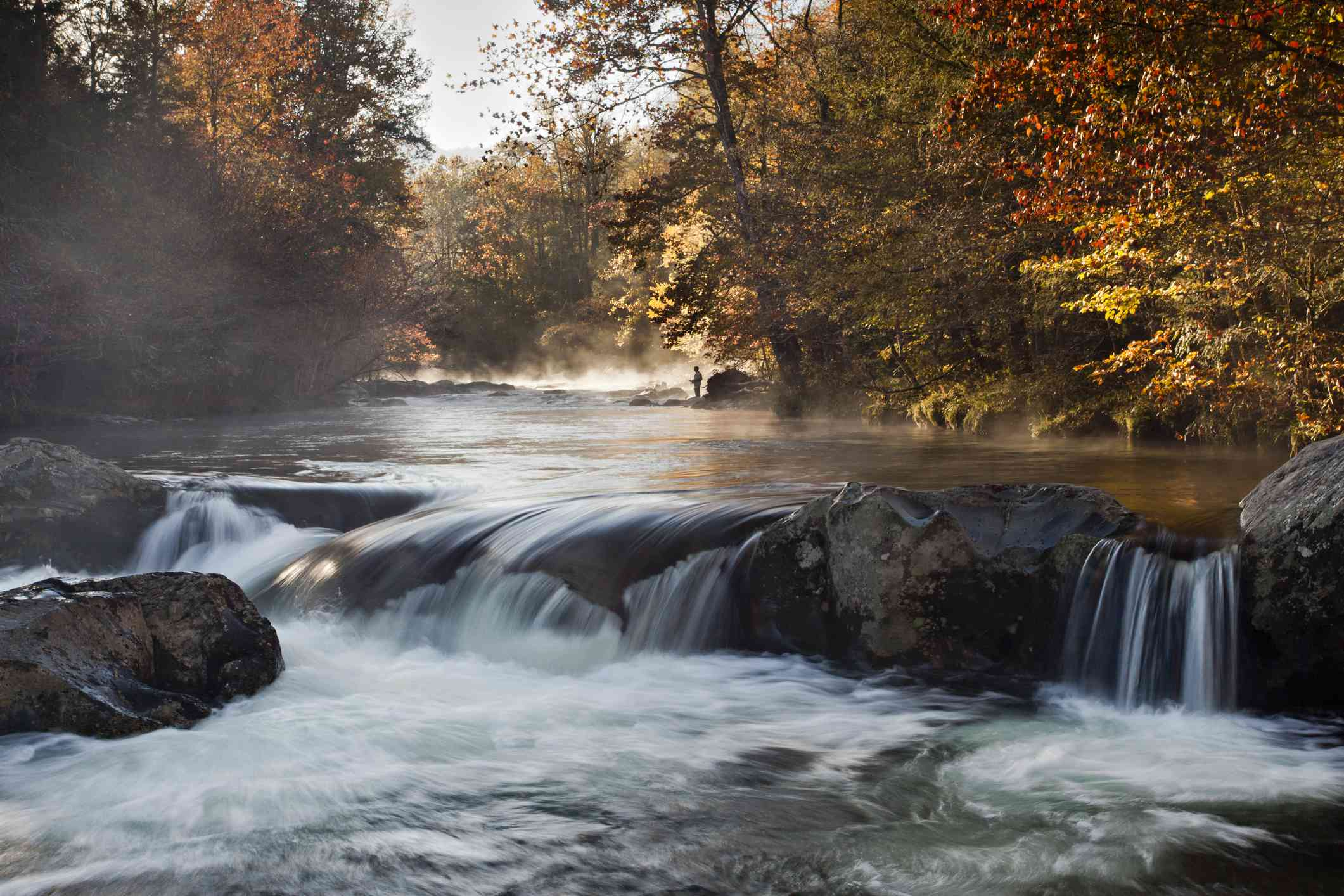 water rushing over large rocks surrounded by trees in autumn shades of red and orange wit a fisherman in the distance