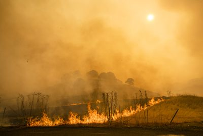 Flames and smoke from wildfires cover the landscape in California