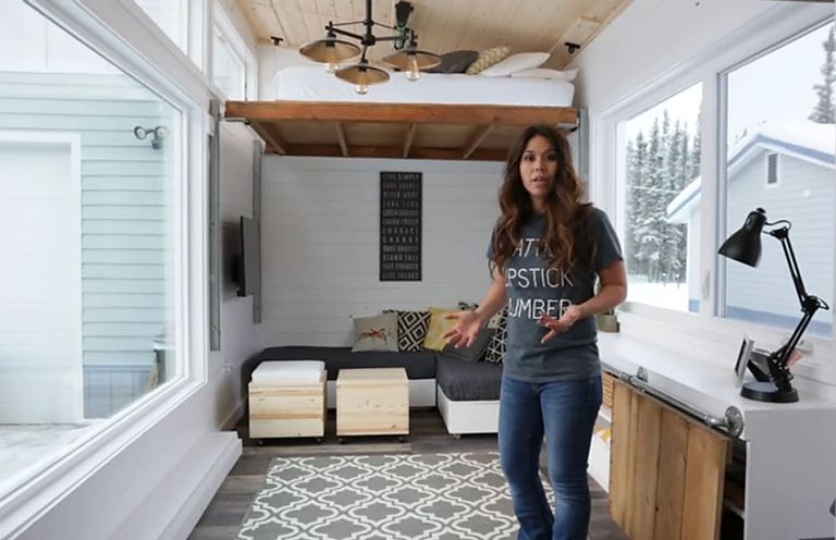 Ana White standing in her tiny home living space with the elevator bed at full height in the background