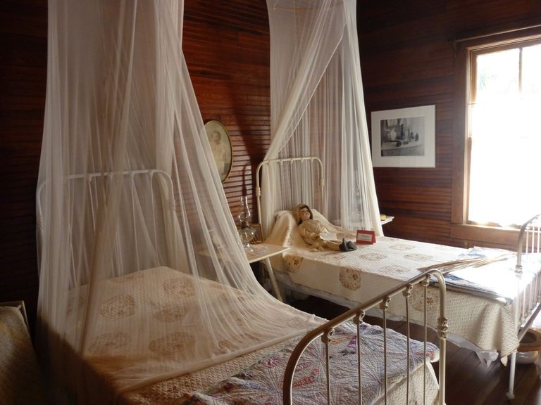 A wood-paneled room with two small beds, both with a netting canopy