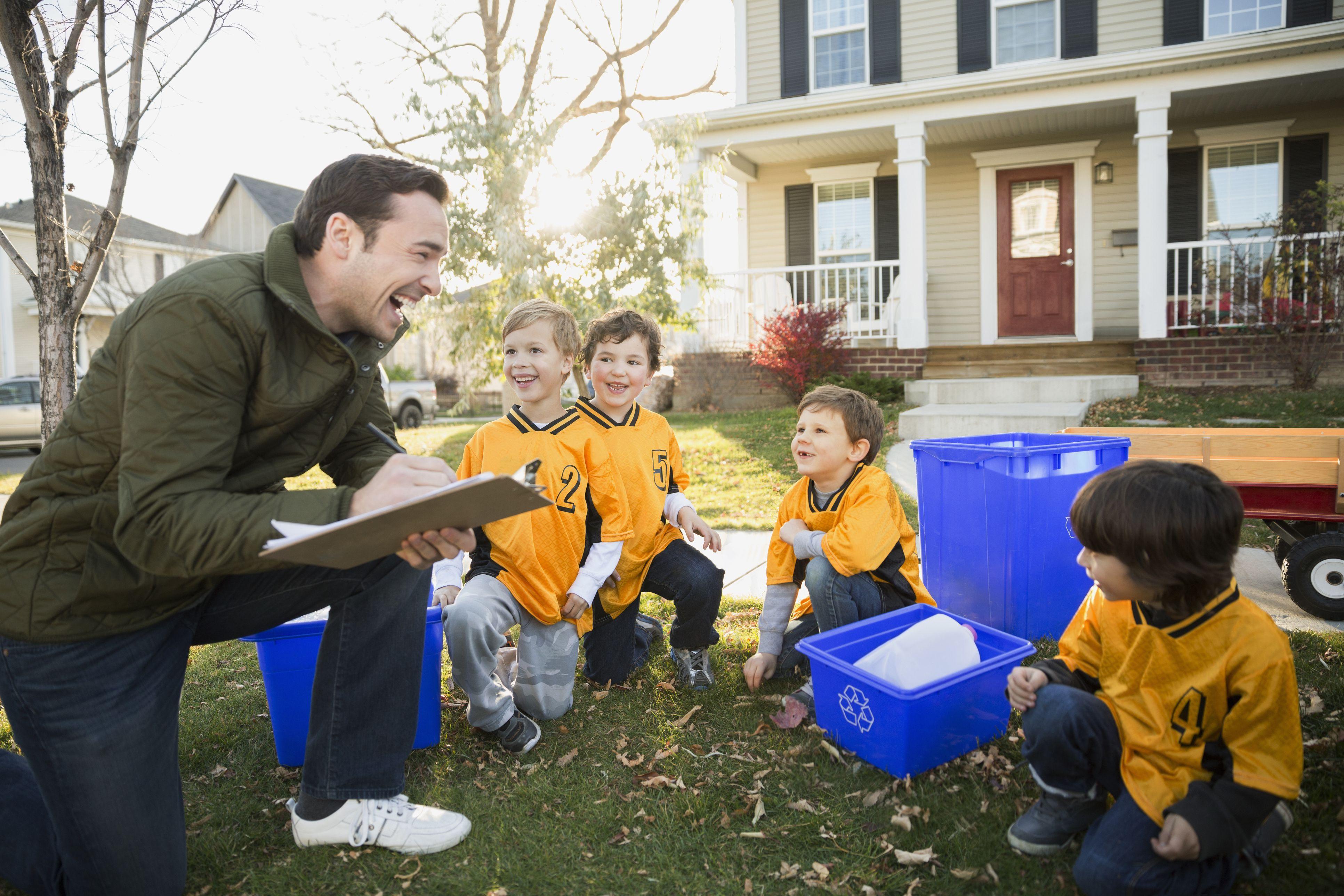 Coach and boys sports team gathering recycling neighborhood